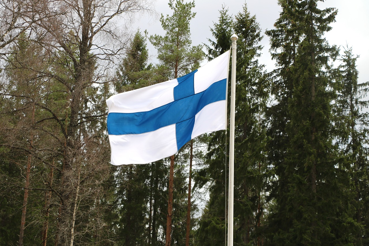 the Finnish flag flying with trees in the background